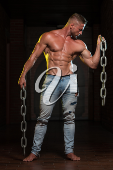 Healthy Young Bodybuilder Exercising Biceps With Chains