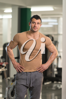Healthy Young Man in Brown T-shirt Standing Strong and Flexing Muscles - Muscular Athletic Bodybuilder Fitness Model Posing After Exercises