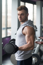 Young Man Working Out Biceps In Gym - Dumbbell Concentration Curls