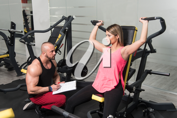 Personal Trainer Showing Young Woman How To Train Shoulders With Dumbbels In The Gym