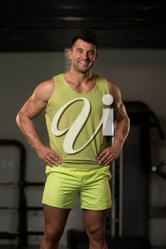 Handsome Young Man Standing Strong in Green T-shirt and Flexing Muscles - Muscular Athletic Bodybuilder Fitness Model Posing After Exercises