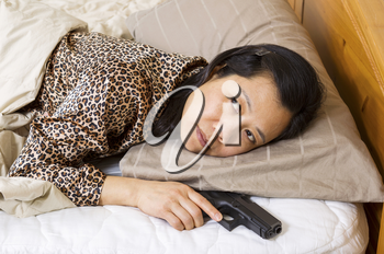 Horizontal photo of mature woman holding personal weapon, pistol, while in bed