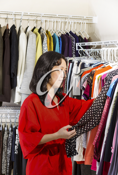 Vertical portrait of mature Asian woman, dressed in red bath robe, in walk-in closet inspecting her clothing before wearing