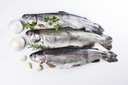 Fresh fish being prepared for dinner with herbs next to them on white background