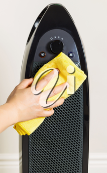 Vertical photo of female hand cleaning home air purifier with yellow microfiber rag with wall in background