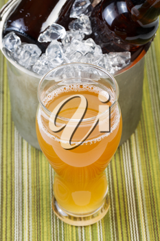 Closeup vertical photo of tall glass filled with golden color beer with bottled beer in ice bucket in background