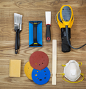 Overhead view of sanding and painting equipment positioned on rustic wooden boards.  Items include electric sander, mask, stir stick, sand paper, scrapper, sanding block, and brushes.