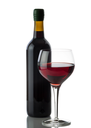 Glass of red wine with full bottle in background on white with reflection
