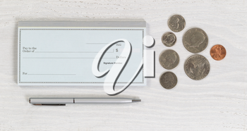 Close up of blank checkbook, silver pen and coins on white wooden desktop. Layout in horizontal format.