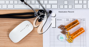Patient medication record form with stethoscope, medication container, capsules, computer keyboard and mouse on wooden desktop. Mouse and keyboard are generic brand items for display purposes only.