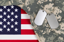 Flag of the United States of America with military identification tags, neck chain, and combat uniform top. Military service concept.