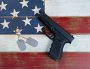 Pistol and military identification tags on top of faded USA flag colors of red, white, and blue on aging boards. Patriotic concept with gun rights.
