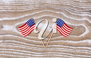 Small USA flags on white rustic wood. Fourth of July holiday concept for United States of America.