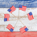 Small USA flags forming pinwheel formation on red, white and blue rustic boards. Fourth of July holiday concept for United States of America.