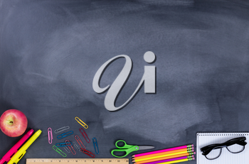 Back to school concept with student supplies on lower part of chalkboard.
