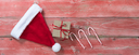 Rustic red wooden background for Christmas concept with gift box, Santa cap and candy canes. Overhead view with copy space.