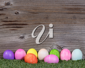 Colorful Easter egg decorations lying on grass with rustic wood in background.