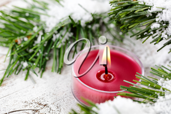 Select focus of glowing candle for Christmas holiday with evergreen and snow