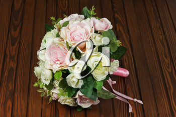Beautiful wedding bouquet from white and pink roses on wooden background.