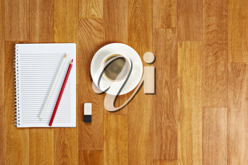 Blank notepad with office supplies and cup of coffee on wooden table. Above view.