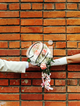 Two hands holding wedding bouquet against a brick wall.
