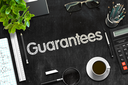 Black Chalkboard with Guarantees. 3d Rendering. Toned Illustration.