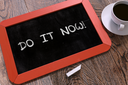 Handwritten Do It Now - Motivation Quote on a Red Chalkboard. Top View Composition with Chalkboard and White Cup of Coffee.