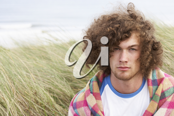 Young Man Standing In Sand Dunes Wrapped In Blanket
