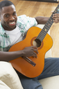 Young Man Relaxing Sitting On Sofa Playing Acoustic Guitar