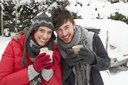 Young couple in snow with car