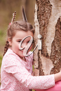 Young Girl Hugging Tree In Forest