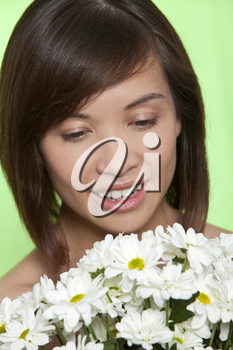 A naturally beautiful oriental woman make up free and holding a bunch of white flowers