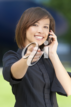 A beautiful young oriental woman with a wonderful smile chatting on her smart cell phone.