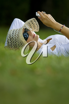 A beautiful dark haired woman laying in a sunlit wooded glade listening to her mp3 player