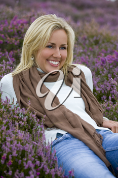 A beautiful blond haired blue eyed young woman laying amongst flowering heather and laughing