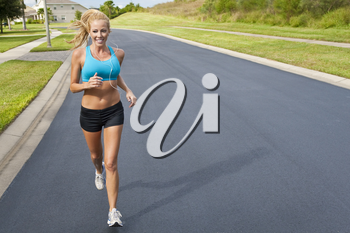 A beautiful fit and healthy blond woman road running while listening to music on her portable mp3 player