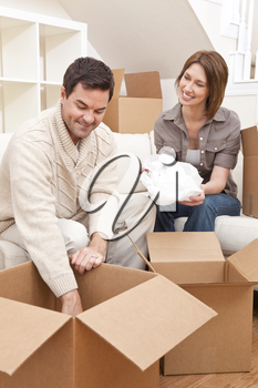 Happy couple in their thirties unpacking or packing boxes and moving into a new home.