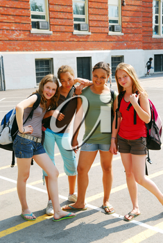 Portrait of a group of young smiling school girls in schoolyard