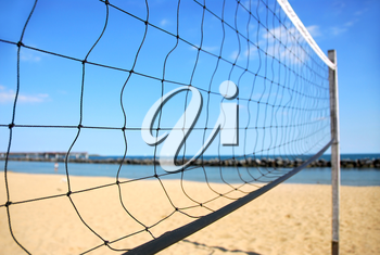 Beach volleyball net in perspective on a sandy beach