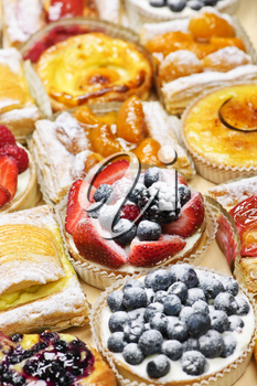 Background of assorted fresh sweet tarts and pastries