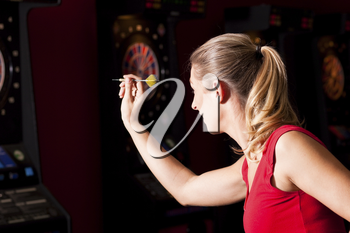 Woman playing darts aiming with the dart to hit the target