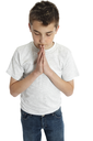 A pre teen boy with hands together in prayer, worship, devotion or thanksgiving,