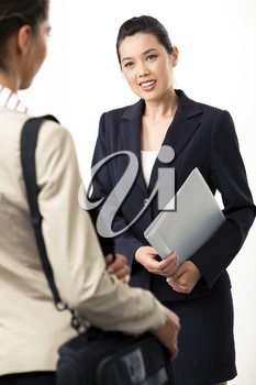 Portrait of elegant woman in suit looking at business partner standing aback and communicating with her