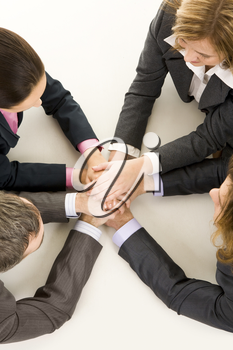 Image of business people keeping hands on top of each other at workplace