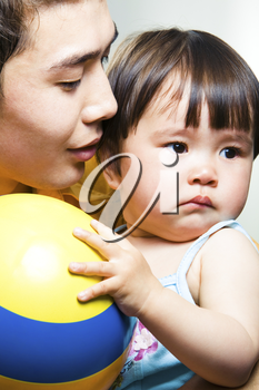 Photo of adorable small girl holding the ball with her daddy near by