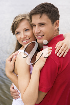 Photo of happy couple looking aside and embracing outdoors