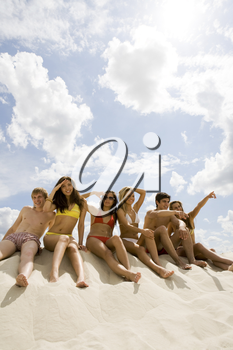 Portrait of teens sitting on sand and looking around