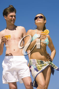 Portrait of relaxing woman in sunglasses and bikini holding cocktail in hand with handsome man standing near by