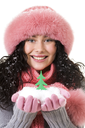 Cheerful woman in pink winter fur cap looking at camera with toy firtree on her palms