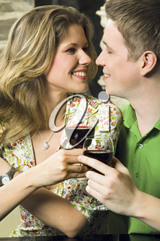 Young couple is holding the glasses of red wine in a restaurant